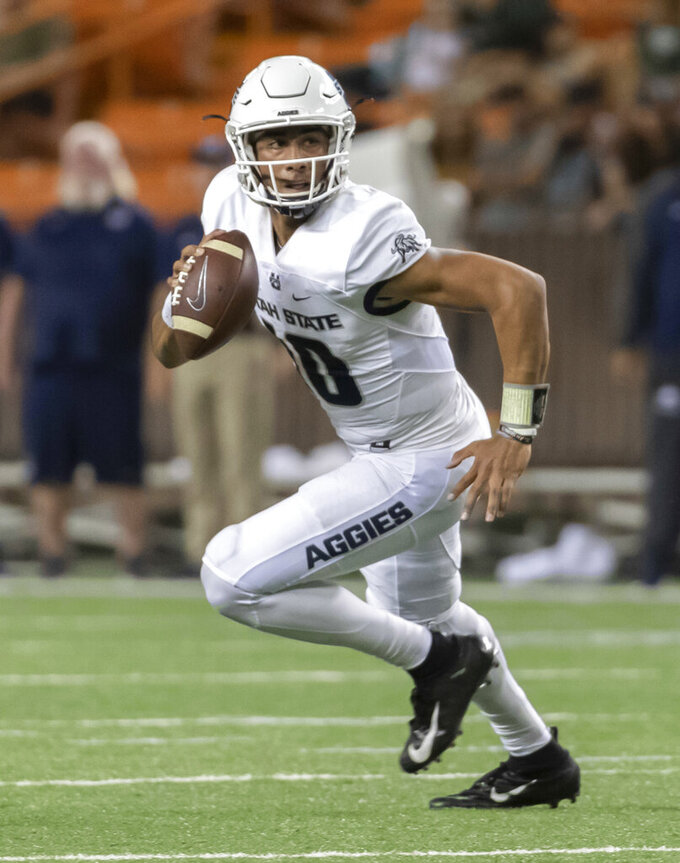 FILE - In this Saturday, Nov. 3, 2018, file photo, Utah State quarterback Jordan Love rolls out looking for an open receiver in the first half of an NCAA college football game against Hawaii in Honolulu. Love, who posted big numbers a season ago, is now being hyped for the Heisman Trophy. (AP Photo/Eugene Tanner, File)