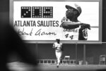 A new sign showing the number of Hank Aaron's home runs provides a background as he runs off the field after the eighth inning of the first game of the doubleheader with the Cincinnati Reds at Atlanta Stadium, Sept. 10, 1973. (AP Photo)