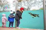 Children visit the penguins at London Zoo in Regent's Park, London, Monday April 12, 2021. Millions of people in England will get their first chance in months for haircuts, casual shopping and restaurant meals on Monday, as the government takes the next step on its lockdown-lifting road map. (Aaron Chown/PA via AP)