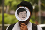 A human rights activist for Amnesty International holds a mask of Thai pro-democracy leader Sirawith Seritiwat during a  protest at police headquarter in Bangkok, Thailand, Wednesday, July 3, 2019. Rights groups are urging Thai authorities to investigate attacks against pro-democracy activists after one was beaten and left unconscious on a sidewalk last week. (AP Photo/Sakchai Lalit)
