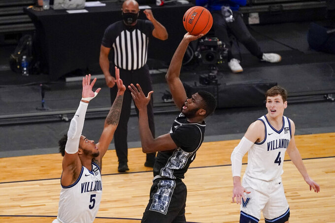 Georgetown center Qudus Wahab, center, goes to the basket against Villanova guard Justin Moore (5) during the first half of an NCAA college basketball game in the quarterfinals of the Big East conference tournament, Thursday, March 11, 2021, in New York. (AP Photo/Mary Altaffer)
