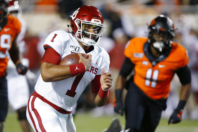 Oklahoma quarterback Jalen Hurts (1) carries past Oklahoma State linebacker Amen Ogbongbemiga (11) for a touchdown in the first half of an NCAA college football game in Stillwater, Okla., Saturday, Nov. 30, 2019. (AP Photo/Sue Ogrocki)