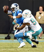 Carolina Panthers' Cam Newton (1) is sacked by Miami Dolphins' Robert Quinn (94) in the first half of a preseason NFL football game in Charlotte, N.C., Friday, Aug. 17, 2018. (AP Photo/Mike McCarn)