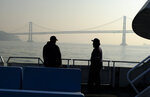A pair of deckhands on a commuter ferryboat talk as the San Francisco-Oakland Bay Bridge is obscured by wildfire smoke and haze Monday, Nov. 12, 2018, in San Francisco. (AP Photo/Eric Risberg)