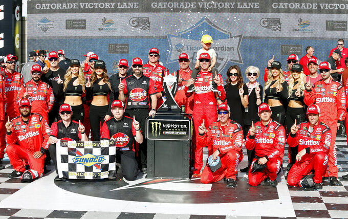 Kyle Busch, with his son Brexton, center, and his race team celebrate in victory lane after winning the NASCAR Cup Series auto race at ISM Raceway, Sunday, March 10, 2019, in Avondale, Ariz. (AP Photo/Ralph Freso)