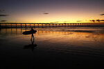 FILE - In this Nov. 7, 2017 file photo a surfer walks out of the surf as the sun sets behind Ocean Beach pier in San Diego. California Gov. Jerry Brown announced Monday, Aug. 20, 2018 that he signed a bill making surfing the official state sport. (AP Photo/Gregory Bull, File)