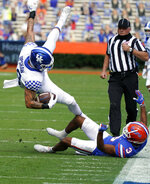 Kentucky tight end Keaton Upshaw, left, is upended by Florida defensive back Marco Wilson (3) after a reception during the first half of an NCAA college football game, Saturday, Nov. 28, 2020, in Gainesville, Fla. (AP Photo/John Raoux)