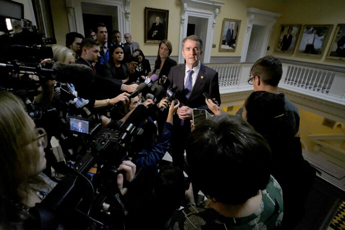 Virginia Giovernor Ralph Northam, center, is surrounded by media outside his office at the State Capitol in Richmond, Va., Wednesday, Nov. 6, 2019. Northam had just left a meeting with his Cabinet and was questioned about the previous night's election results which gave Democrats control of the Virginia House of Delegates and Senate.   (Bob Brown/Richmond Times-Dispatch via AP)