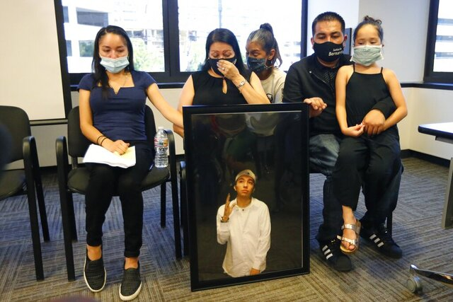 FILE - In this Thursday, July 9, 2020, file photo, Lucy Carbajal, center left, sits behind a photograph of her son Bernardo Palacios-Carbajal while other family members look on during a news conference at their attorney's office in Salt Lake City. District Attorney Sim Gill says Utah police officers were legally justified in firing more than 30 times and killing an armed man as he ran away. The case has become a rallying point for protesters in the state amid a national wave of dissent against police brutality. Gill said 22-year-old Bernardo Palacios-Carbajal was shot as he ran from Salt Lake City police officers who were investigating a gun-threat call and had yelled for him to drop a gun. The family of a Utah man who was killed and shot at more than 30 times as he ran from police filed a lawsuit against the Salt Lake City police department Friday, Sept. 25, 2020. (AP Photo/Rick Bowmer, File)