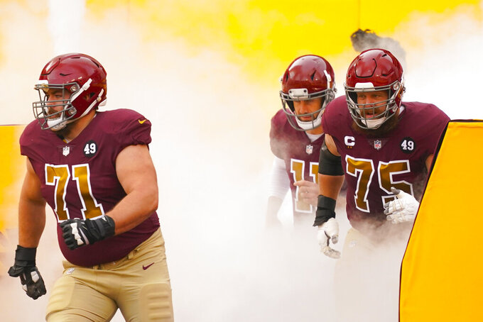 Members of the Washington Football Team taking the field, from l-r., offensive guard Wes Schweitzer (71), quarterback Alex Smith (11) and offensive guard Brandon Scherff (75) before the start of the first half of an NFL football game, Sunday, Nov. 22, 2020, in Landover. (AP Photo/Andrew Harnik)
