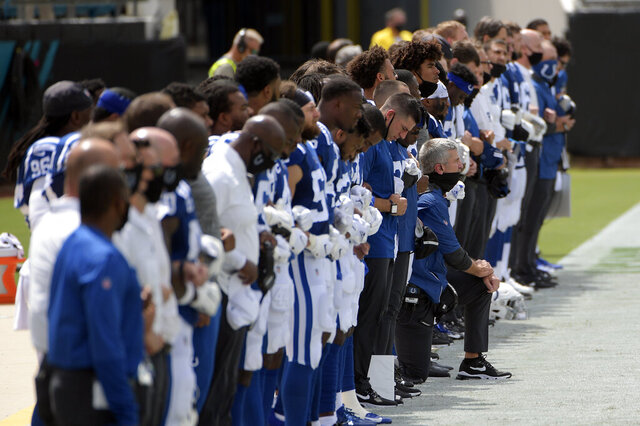 Indianapolis Colts head coach Frank Reich, center, kneels the national anthem during the first half of an NFL football game, Sunday, Sept. 13, 2020, in Jacksonville, Fla. (AP Photo/Phelan M. Ebenhack)