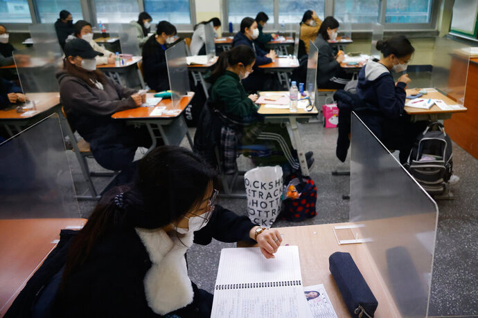 A student checks the time as others wait for the start of the annual college entrance examination amid the coronavirus pandemic at an exam hall in Seoul, South Korea, Thursday, Dec. 3, 2020. South Korean officials are urging people to remain at home if possible and cancel gatherings as about half a million students prepare for a crucial national college exam. (Kim Hong-Ji/Pool Photo via AP)