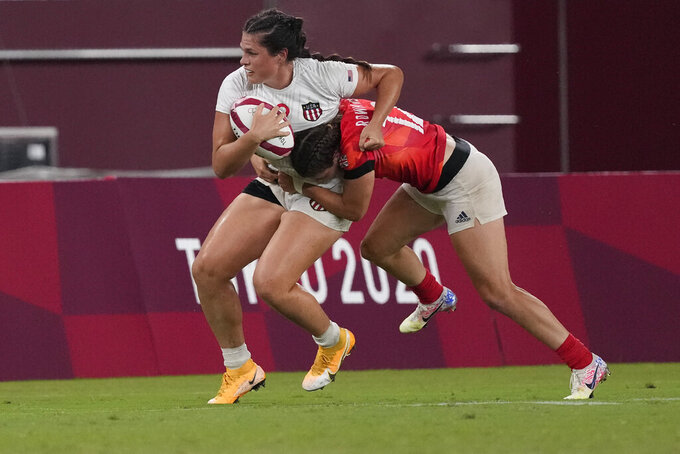 Ilona Maher of the United States is tackled by Britain's Helena Rowland in their women's rugby sevens quarterfinal match at the 2020 Summer Olympics, Friday, July 30, 2021 in Tokyo, Japan. (AP Photo/Shuji Kajiyama)
