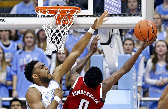 North Carolina's Brandon Huffman blocks while North Carolina State's DJ Funderburk (0) shoots during the first half of an NCAA college basketball game in Chapel Hill, N.C., Tuesday, Feb. 5, 2019. (AP Photo/Gerry Broome)