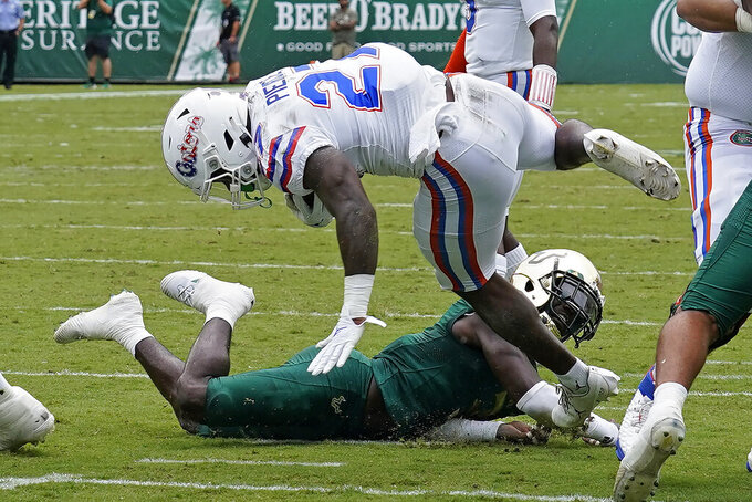 Florida running back Dameon Pierce (27) gets tripped up by South Florida safety Vincent Davis (3) but still scores a touchdown during the first half of an NCAA college football game Saturday, Sept. 11, 2021, in Tampa, Fla. (AP Photo/Chris O'Meara)