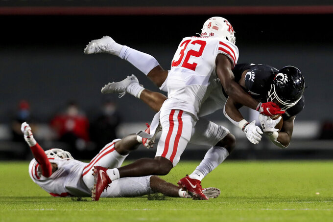 Houston safety Gervarrius Owens (32) tackles Cincinnati running back Gerrid Doaks, right, as he is upended by Houston cornerback Marcus Jones, bottom left, during the second half of an NCAA college football game, Saturday, Nov. 7, 2020, in Cincinnati. (AP Photo/Aaron Doster)