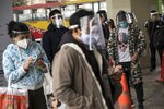 Commuters wearing protective face masks and face shields wait to enter a train station in Lima, Peru, Saturday, July 25, 2020. Peru ordered the mandatory wearing of protective face masks and shields on public transportation amid the new coronavirus pandemic.(AP Photo/Rodrigo Abd)