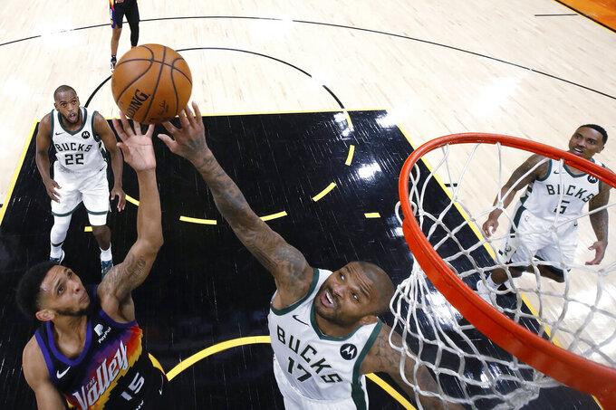 Phoenix Suns' Cameron Payne (15) shoots over Milwaukee Bucks' P.J. Tucker (17) during the first half of Game 1 of basketball's NBA Finals, Tuesday, July 6, 2021, in Phoenix. (Christian Petersen/Pool Photo via AP)