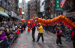 Participants march with a dragon caricature during the Lunar New Year parade in Manhattan's Chinatown neighborhood, in New York, Sunday, Feb. 9, 2020. (AP Photo/Craig Ruttle)