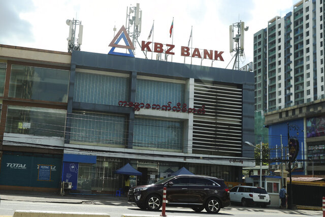A vehicle passes by in front of a Kanbawza bank branch Thursday, Sept. 10, 2020, in Yangon, Myanmar. The Kanbawza Group, or KBZ, is one of Myanmar's largest conglomerates, with businesses in a variety of sectors including construction, finance, manufacturing, agriculture, trading, insurance, aviation and jade and ruby mining and joint ventures with Myanmar Economic Holdings, a huge conglomerate that an Amnesty International report says is supporting military units and individuals involved in human rights abuses. (AP Photo/Thein Zaw)