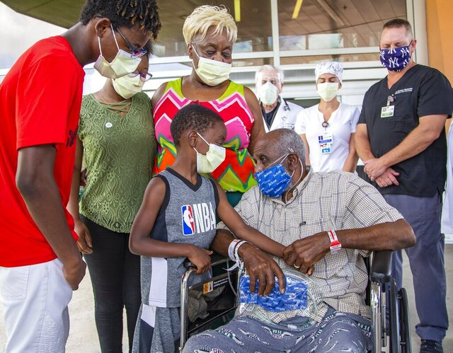 James Gardner, 77, goes home after battling COVID-19 for a month at Jackson South Medical Center, Thursday, Aug. 27, 2020 in Miami. Greeting him outside the hospital is his adopted son Shaquille Gross, 7, and the rest of his family, left to right, Noel Gross, 16, Kendra Gross, 17, his wife Maggie Gross Gardner, 75, as the medical staff at the hospital sends his home.(Al Diaz/Miami Herald via AP)