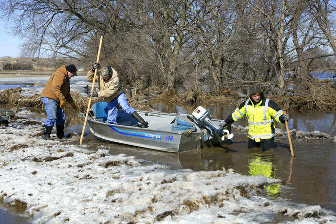 Tom Witke, left, his son Chad, center, and Nick Kenny, launch a boat into the swollen waters of the North Fork of the Elkhorn River, to check on Witke's flooded property, in Norfolk, Neb., Friday, March 15, 2019. Heavy rain falling atop deeply frozen ground has prompted evacuations along swollen rivers in Wisconsin, Nebraska and other Midwestern states. Thousands of people have been urged to evacuate along eastern Nebraska rivers as a massive late-winter storm has pushed streams and rivers out of their banks throughout the Midwest. (AP Photo/Nati Harnik)