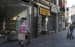 Two older women wear facemasks as they push their walkers on a shopping street, during a partial lifting of coronavirus, COVID-19, regulations in Halle, Belgium, Wednesday, June 24, 2020. (AP Photo/Virginia Mayo)