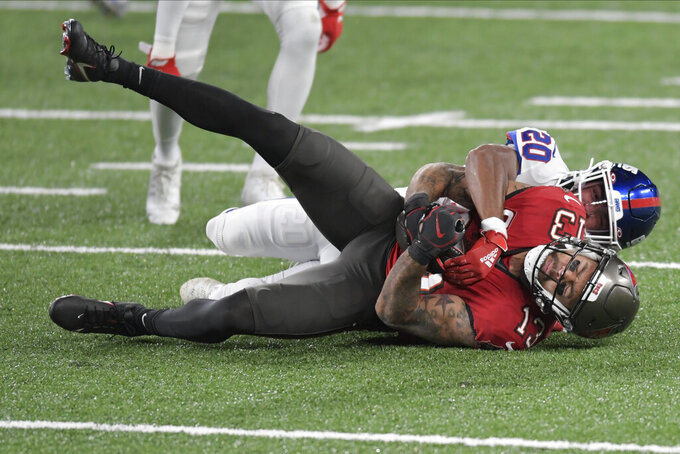 New York Giants' Julian Love (20), top, brings down Tampa Bay Buccaneers' Mike Evans during the second half of an NFL football game, Monday, Nov. 2, 2020, in East Rutherford, N.J. (AP Photo/Bill Kostroun)