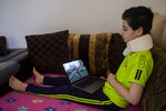 Hoda Kinno, 11, looks at an photograph on a computer that was taken by Associated Press Photographer Hassan Ammar when she was evacuated by her uncle Mustafa in the aftermath of the massive explosion at Beirut port on Aug. 4, at a temporary apartment in Jiyeh, south of Beirut, Lebanon, Tuesday, Sept. 15, 2020. (AP Photo/Hassan Ammar)
