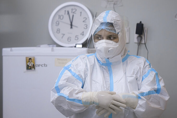 A member of the medical staff adjusts her gloves at the COVID-19 ICU unit of the Marius Nasta National Pneumology Institute in Bucharest, Romania, Thursday, Sept. 23, 2021. Daily new coronavirus infections in Romania, a country of 19 million, have grown exponentially over the last month, while vaccine uptake has declined to worrying lows. Government data shows that 91.5% of COVID-19 deaths in Romania between Sept. 18-23 were people who had not been vaccinated. (AP Photo/Andreea Alexandru)