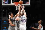 Brooklyn Nets center Jarrett Allen (31) gets his hand in on a rebound as Nets guard Dzanan Musa (13) andn Charlotte Hornets forward Cody Zeller (40) join in the scrum beneath the Nets' basket during the first half of an NBA basketball game, Wednesday, Dec. 11, 2019, in New York. (AP Photo/Kathy Willens)