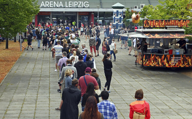 22 August 2020, Saxony, Leipzig: Test persons of a large-scale experiment of the University Medicine Halle/Saale are standing at the entrance in front of the Arena Leipzig. Around 2200 visitors take part in the experiment entitled