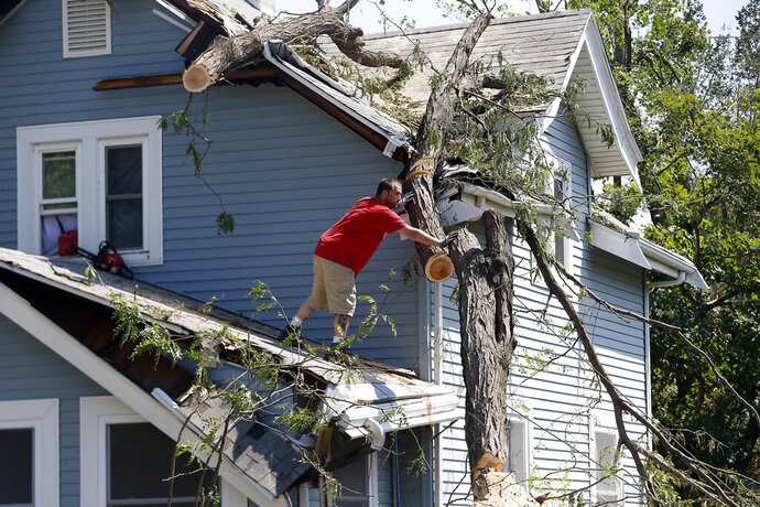 Mike Jacobis pushes a portion of tree trunk away as a neighbor helps on the ground in northwest Cedar Rapids, Iowa, on Wednesday, Aug. 12, 2020. The tree, which fell in Monday's storm, fell and damaged Jacobis' porch and the roof over a second-floor bedroom and closet. (Liz Martin/The Gazette via AP)