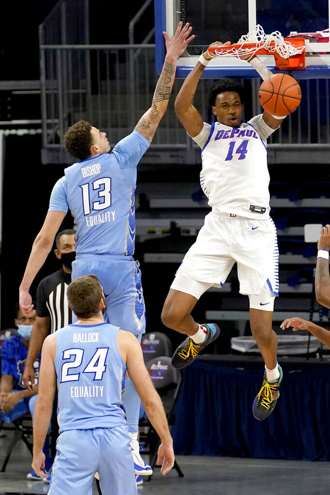DePaul's Nick Ongenda (14) dunks over Creighton's Christian Bishop (13) as Creighton's Mitch Ballock watches during the first half of an NCAA college basketball game Saturday, Jan. 30, 2021, in Chicago. (AP Photo/Charles Rex Arbogast)