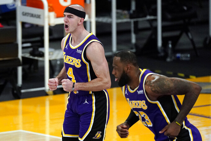Los Angeles Lakers guard Alex Caruso (4) reacts after scoring during the second half of an NBA basketball game against the Portland Trail Blazers Friday, Feb. 26, 2021, in Los Angeles. Los Angeles Lakers forward LeBron James (23) is at right. (AP Photo/Mark J. Terrill)