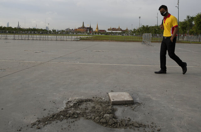 A man walks near a hole at the Sanam Luang field in Bangkok, Thailand, Monday, Sept. 21, 2020. A plaque symbolizing Thailand's transition to democracy has been removed less than 24 hours after it was installed by anti-government demonstrators in a historic royal field. (AP Photo/Sakchai Lalit)