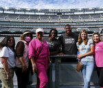 This photo provided by the New York Jets shows New York Jets NFL players Quinnen Williams, center left, and his brother Quincy, center right, posed with unidentified supporters of the Crucial Catch initiative at MetLife Stadium in East Rutherford, N.J., Sunday, Oct. 3, 2021. Brothers Quinnen and Quincy Williams have become leading spokesmen for the NFL's annual Crucial Catch initiative. Their mother, Marquischa Henderson Williams, passed away when Quinnen was 12 years old after losing her second battle with breast cancer. Both players wear a necklace with her picture inside. (New York Jets via AP)