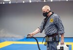 In this Tuesday, June 23, 2020 photo, Paul Heinselman, master instructor at H&H Family Martial Arts Academy, uses a fogger machine to disinfect the mat after class in the Beaver Valley Mall in Monaca, Pa. Contact sports with no contact sounds impossible, but it's become the new normal for martial arts studios throughout the pandemic. Students at H&H Family Martial Arts Academy in Monaca, Beaver County, run to a designated dot spaced six feet away from the next. There will be no interaction with friends as they would on a normal day. Instead, students are expected to keep to themselves — even the five-year-olds.(Emily Matthews/Pittsburgh Post-Gazette via AP)