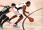 Los Angeles Clippers forward Kawhi Leonard (2) dribbles the ball past Brooklyn Nets forward Rodions Kurucs (00) during the second half of an NBA basketball game Sunday, Aug. 9, 2020, in Lake Buena Vista, Fla. (Kim Klement/Pool Photo via AP)