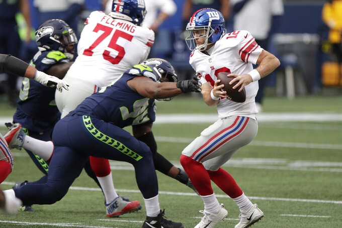 New York Giants quarterback Colt McCoy, right, tries to escape pressure from Seattle Seahawks defensive end Rasheem Green (94) during the first half of an NFL football game, Sunday, Dec. 6, 2020, in Seattle. (AP Photo/Larry Maurer)