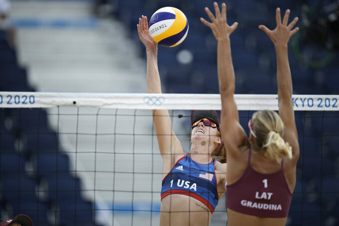 Kelly Claes, left, of the United States, reaches for the ball as Tina Graudina, of Latvia, defends during a women's beach volleyball match at the 2020 Summer Olympics, Monday, July 26, 2021, in Tokyo, Japan. (AP Photo/Felipe Dana)