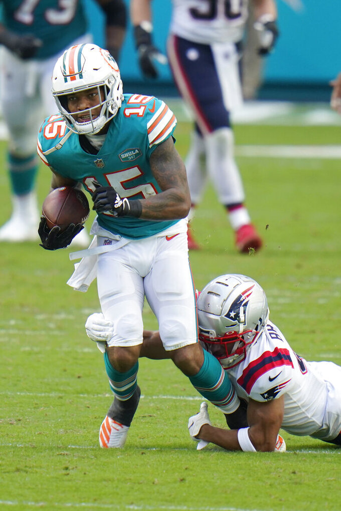 New England Patriots cornerback Myles Bryant (41) tackles Miami Dolphins running back Lynn Bowden (15), during the first half of an NFL football game, Sunday, Dec. 20, 2020, in Miami Gardens, Fla. (AP Photo/Chris O'Meara)