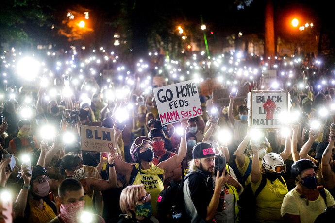 FILE - In this July 20, 2020, file photo, hundreds of Black Lives Matter protesters hold their phones aloft in Portland, Ore. Once hailed as one of the most livable cities in the U.S., Portland, Oregon, is grappling with an uncertain future as it reaches a stunning benchmark: 100 consecutive nights of racial injustice protests marred by vandalism, chaos — and now, the killing of a supporter of President Donald Trump. (AP Photo/Noah Berger, File)