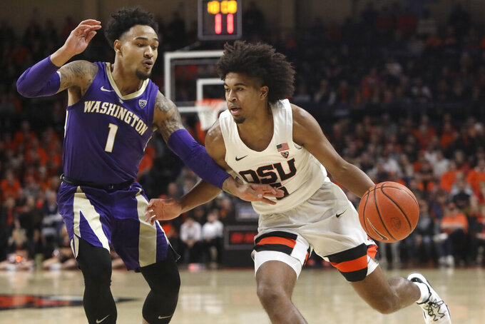 Oregon State's Ethan Thompson, right, is guarded by Washington's David Crisp (1) during the first half of an NCAA college basketball game in Corvallis, Ore., Saturday, Jan. 26, 2019. (AP Photo/Amanda Loman)
