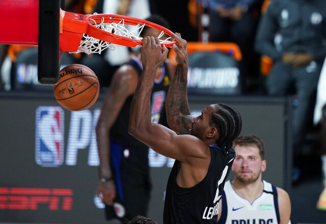 Dallas Mavericks' Luka Doncic (77) watches as Los Angeles Clippers' Kawhi Leonard (2) scores during the second half of an NBA first round playoff game Sunday, Aug. 30, 2020, in Lake Buena Vista, Fla. (AP Photo/Ashley Landis)