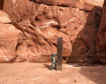 FILE - In this Nov. 18, 2020, file photo provided by the Utah Department of Public Safety, a Utah state worker stands next to a metal monolith in the ground in a remote area of red rock in Utah. The mysterious silver monolith that was placed in the Utah desert has disappeared less than 10 days after it was spotted by wildlife biologists performing a helicopter survey of bighorn sheep, federal officials and witnesses said. The Bureau of Land Management said it had received credible reports that the three-sided stainless steel structure was removed on Nov. 27.  (Utah Department of Public Safety via AP, File)
