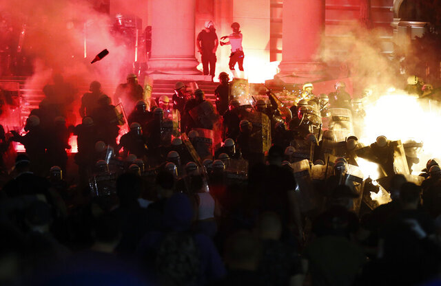 Protesters clash with riot police on the steps of the Serbian parliament during a protest in Belgrade, Serbia, Friday, July 10 2020. Hundreds of demonstrators tried to storm Serbia's parliament on Friday, clashing with police who fired tear gas during the fourth night of protests against the president's increasingly authoritarian rule. (AP Photo/Darko Vojinovic)
