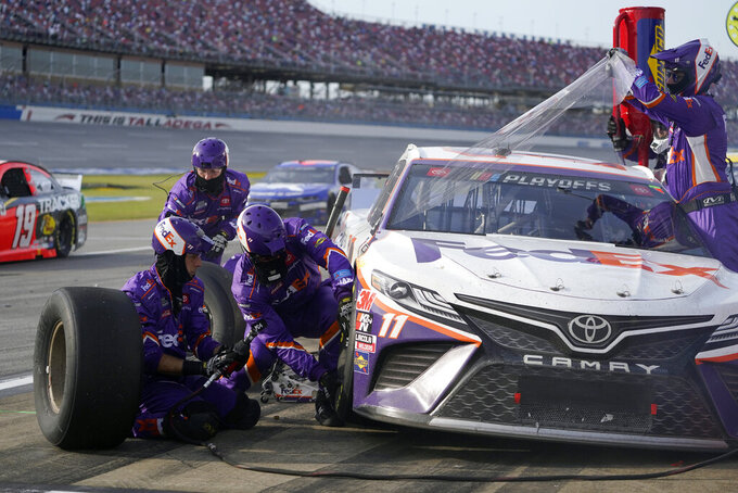 Pit crew members work to get Denny Hamlin back on the track during the YellaWood 500 NASCAR auto race at Talladega Superspeedway, Sunday, Oct. 4, 2020, in Talladega, Ala. Hamlin won the race. (AP Photo/John Bazemore)