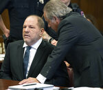 Harvey Weinstein, left, talks with his attorney Benjamin Brafman during his hearing at a courtroom in New York, Thursday, Oct. 11, 2018. Manhattan's district attorney dropped part of the criminal sexual assault case against Weinstein on Thursday after evidence emerged that cast doubt on the account one of his three accusers provided to the grand jury.  (Steven Hirsch /New York Post via AP, Pool)