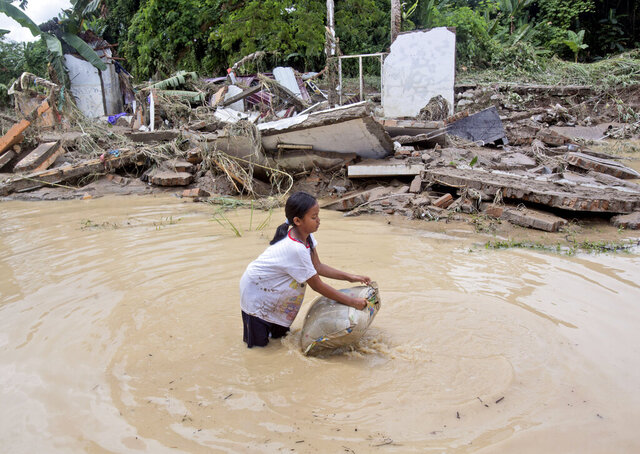 A young girl washes a pillow in flood water near ruins of houses at a neighborhood affected by the flood in Medan, North Sumatra, Indonesia, Friday, Dec. 4, 2020. Torrential rains in the country's third largest city swelled rivers and flooded thousands of homes leaving a number of people killed and missing. (AP Photo/Binsar Bakkara)